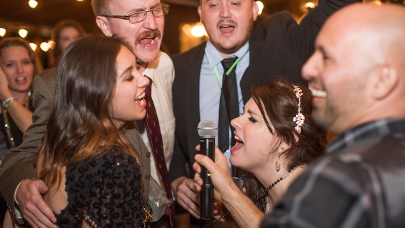 A crowd singing into a microphone at one of our corporate events.